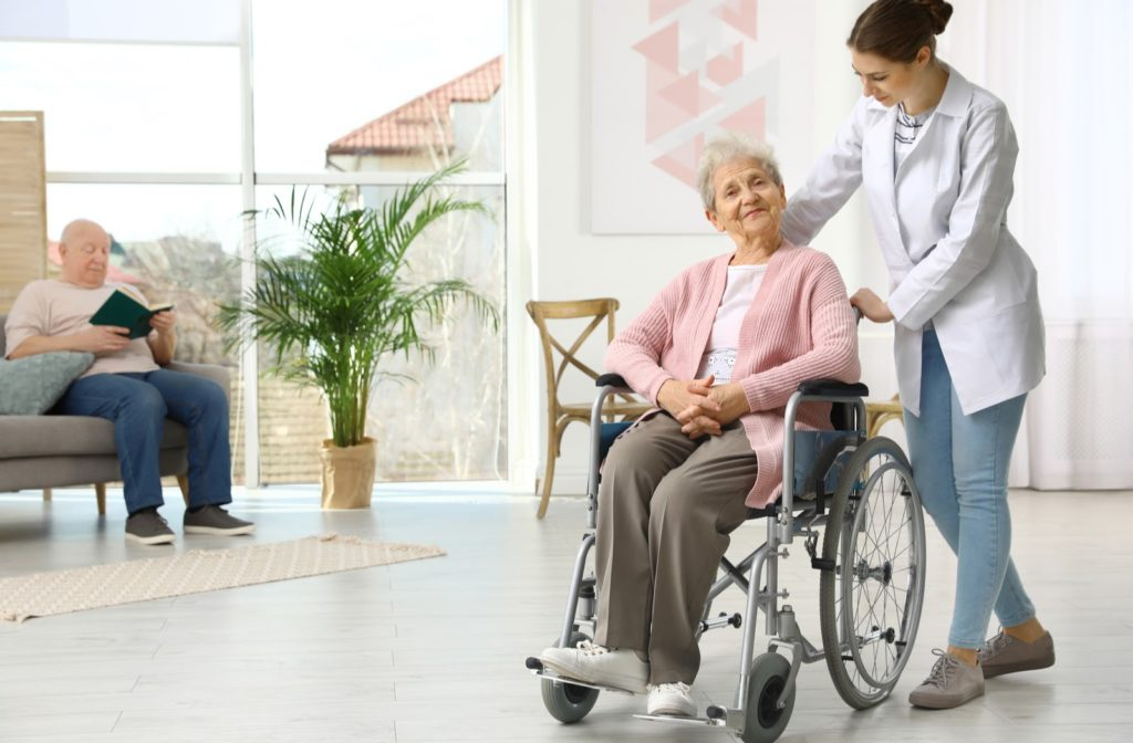 Nurse assisting elderly women in wheelchair at senior community with a man reading book on chair in background
