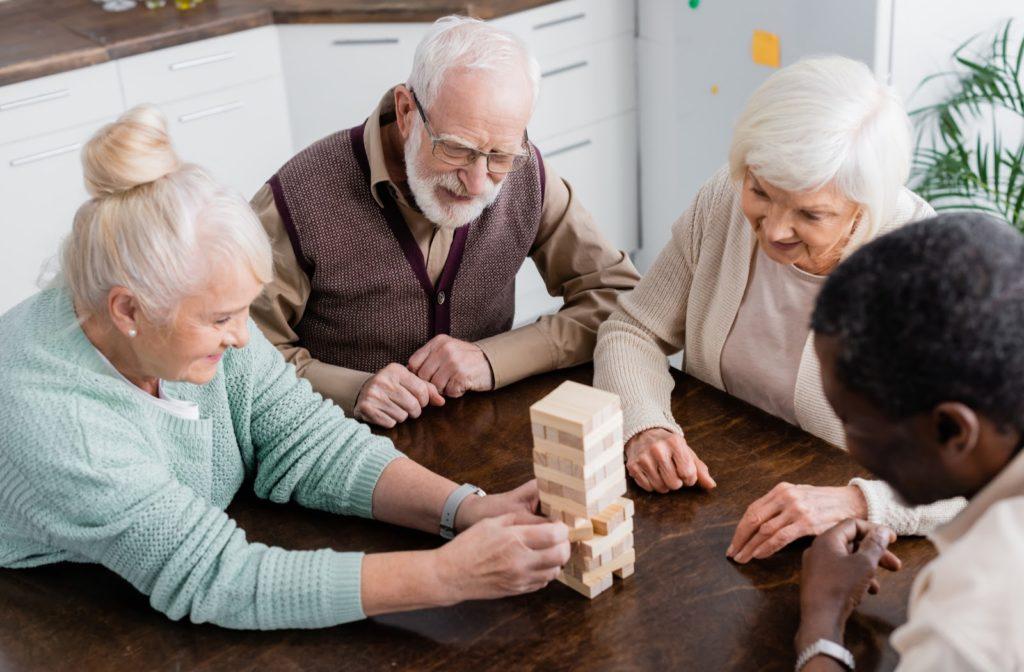 Happy seniors playing JENGA at table in senior community.